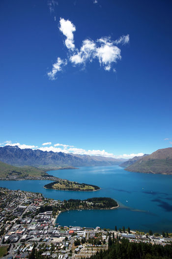 High Angle View Of Lake And Mountains Against Blue Sky