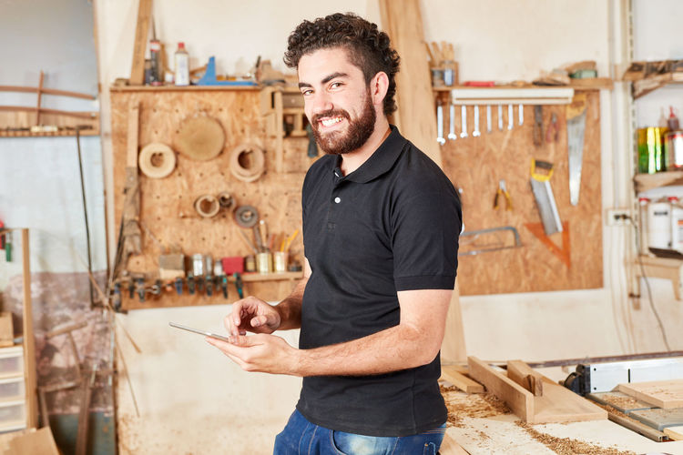 Portrait of smiling carpenter using mobile phone at workshop