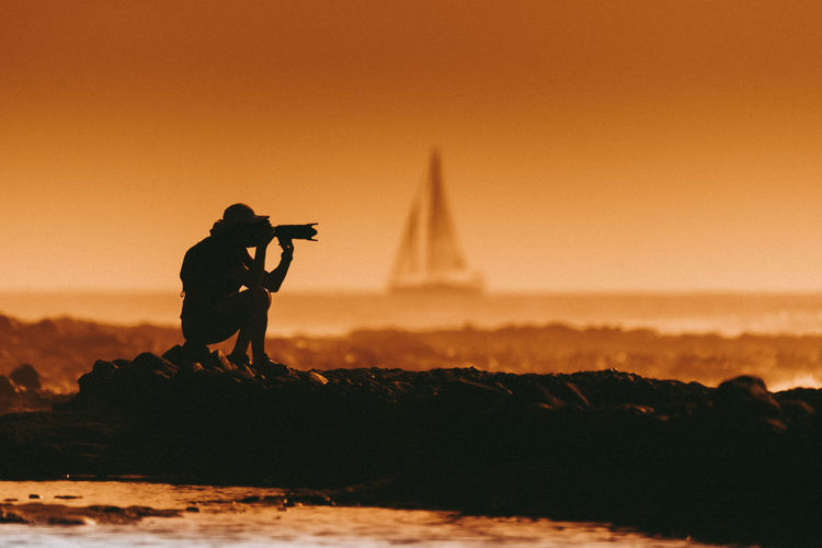 Silhouette of man photographing at beach against sky during sunset