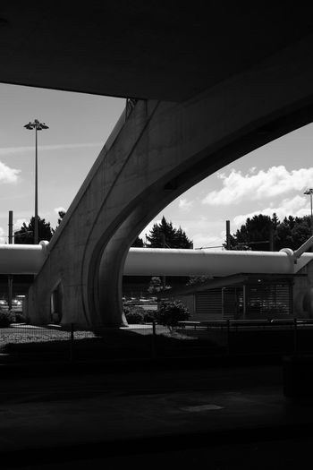 Bridge over street in city against sky