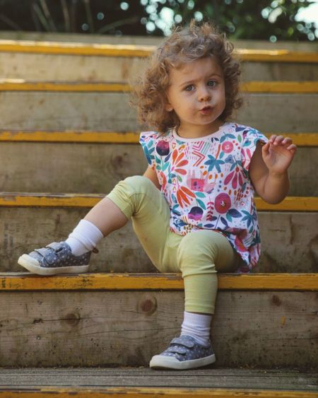 Cute girl looking away while sitting on steps