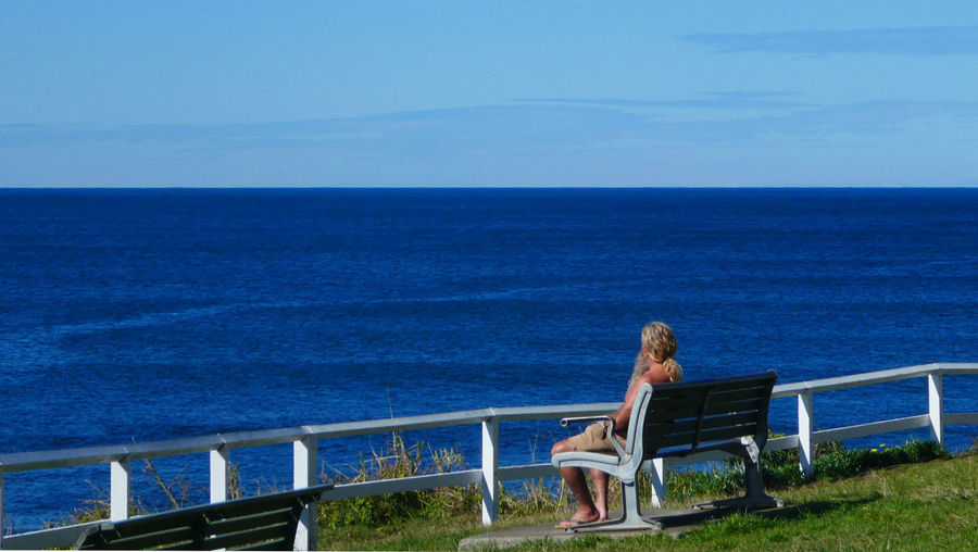 Woman sitting on chair by sea against blue sky