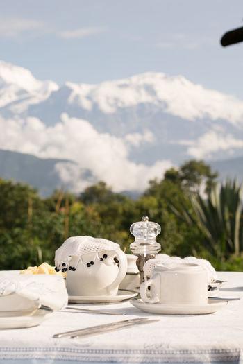 White tea on table against mountains