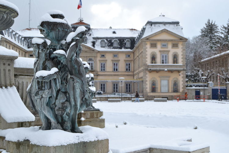 Statues on snow by buildings against sky during winter