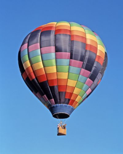 Low angle view of people in hot air balloon against clear blue sky
