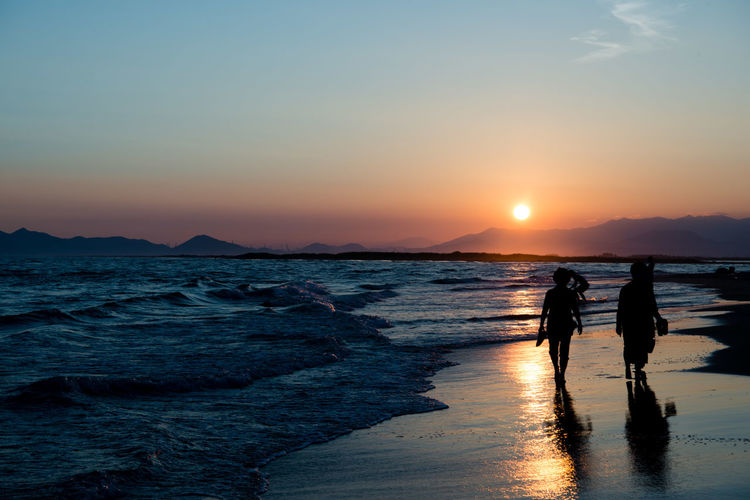 Beach Beauty In Nature Family Land Leisure Activity Lifestyles Men Nature Outdoors People Real People Reflection Scenics - Nature Sea Sky Sun Sunset Togetherness Two People Water Women