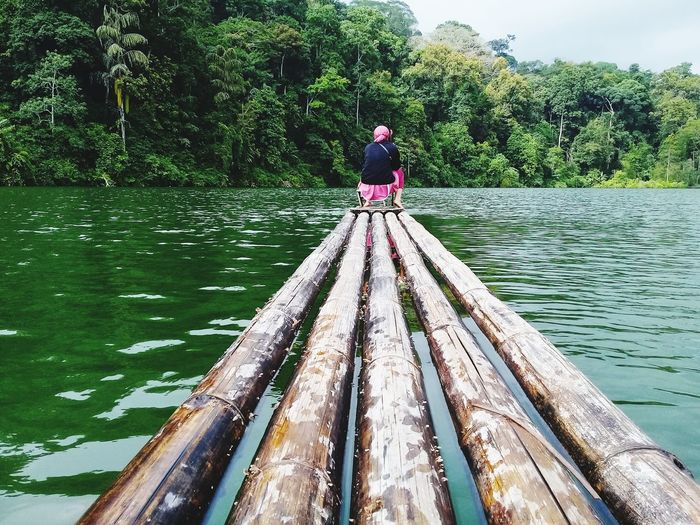 Rear View Of Woman Sitting On Bamboo Boat In Lake Against Trees