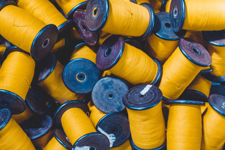 Full frame shot of yellow thread spools