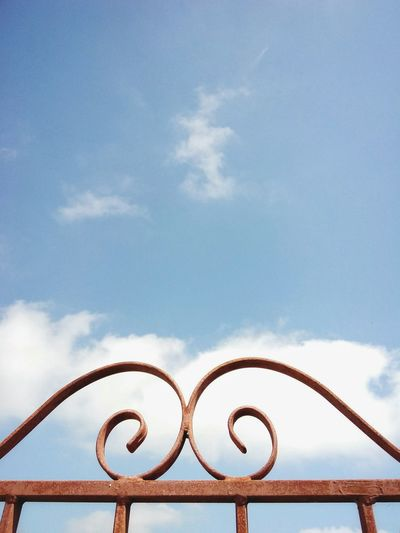 Close-up of metallic gate against sky