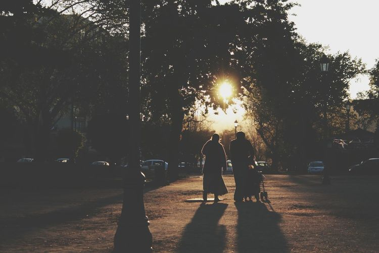 Rear View Of Silhouette Man And Woman With Baby Carriage Walking On Road