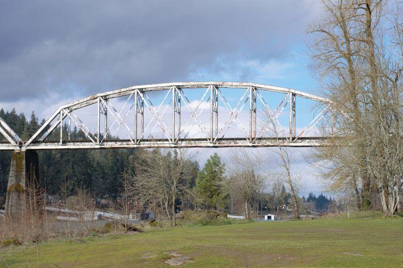 Arch bridge on field against sky