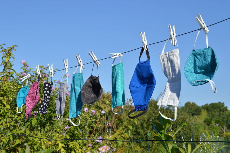 Clothes drying on clothesline against blue sky