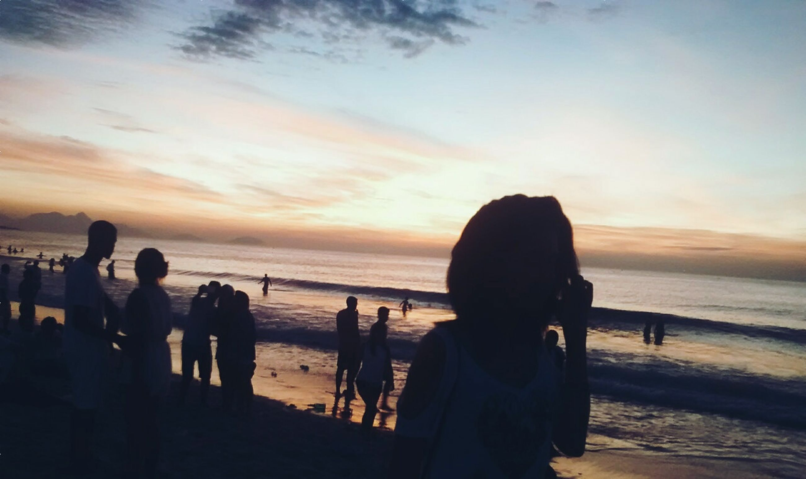 sea, horizon over water, beach, sunset, water, shore, sky, silhouette, lifestyles, leisure activity, men, scenics, beauty in nature, person, vacations, orange color, sand, nature, tranquil scene