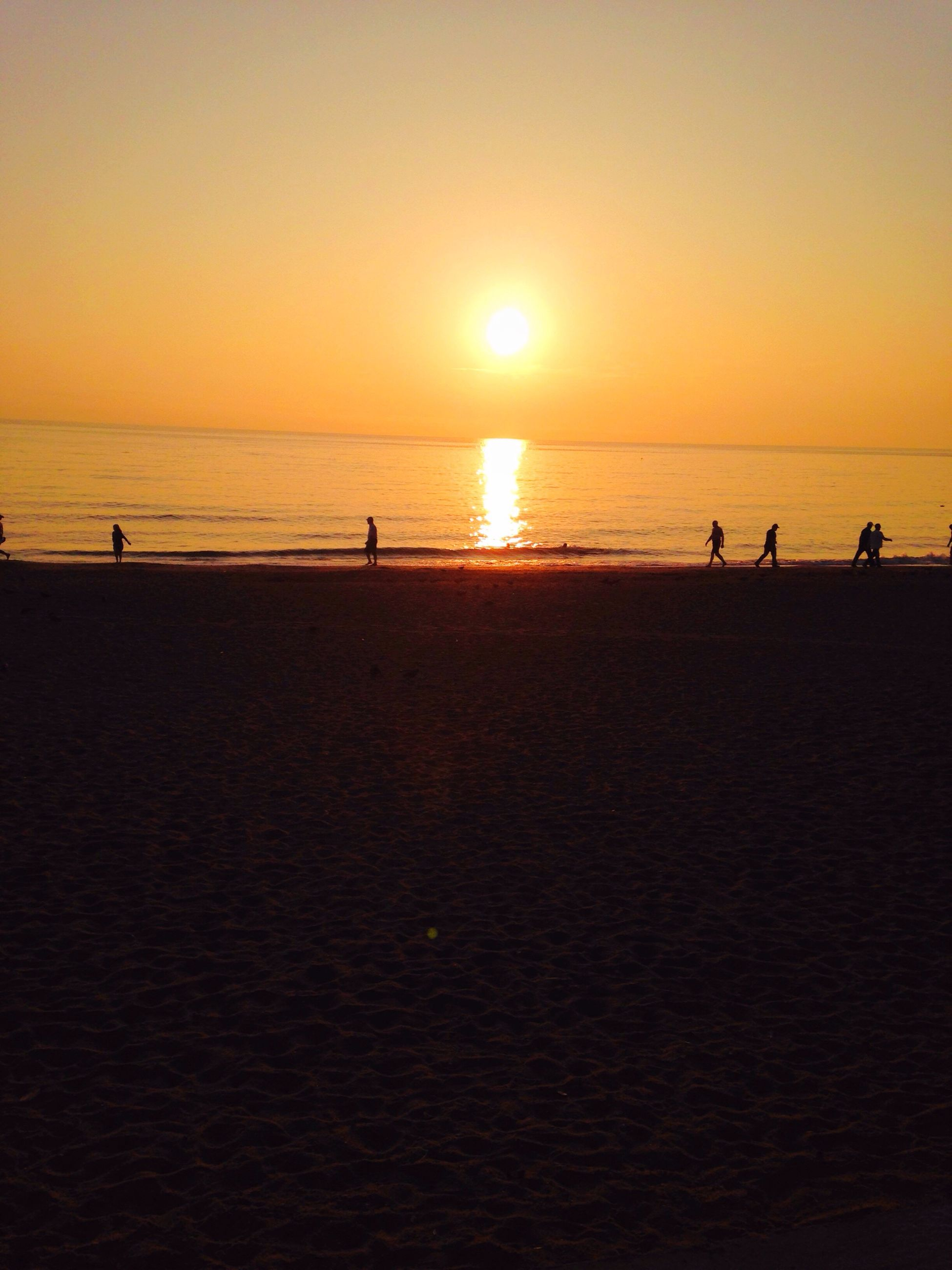 sunset, sea, water, horizon over water, beach, orange color, sun, scenics, beauty in nature, tranquil scene, shore, tranquility, idyllic, vacations, nature, leisure activity, medium group of people, unrecognizable person, sky, tourist, lifestyles, tourism, outdoors, coastline, mixed age range, travel destinations, enjoyment