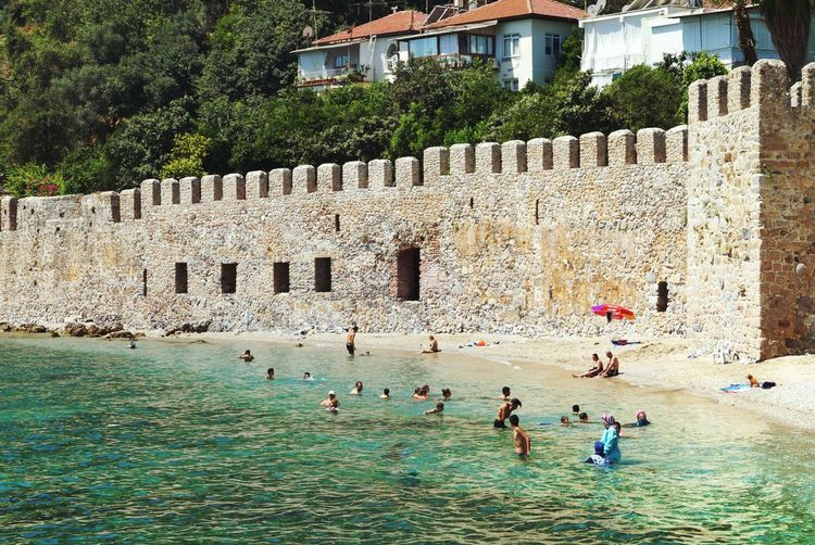 Abandoned Beaches Hidden Beach Where The Locals Go For A Swim High Fortress Walls In The Background Women In Burka Swimming Suits bikini 😊 Clear Water Bay Sunny Day Geo Tag : Ancient Shipyard Beside The Harbor Of Alanya Turkey Showcase July Hidden Gems