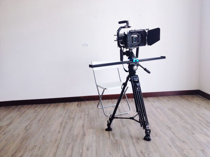 Tripod camera on floor against wall in room