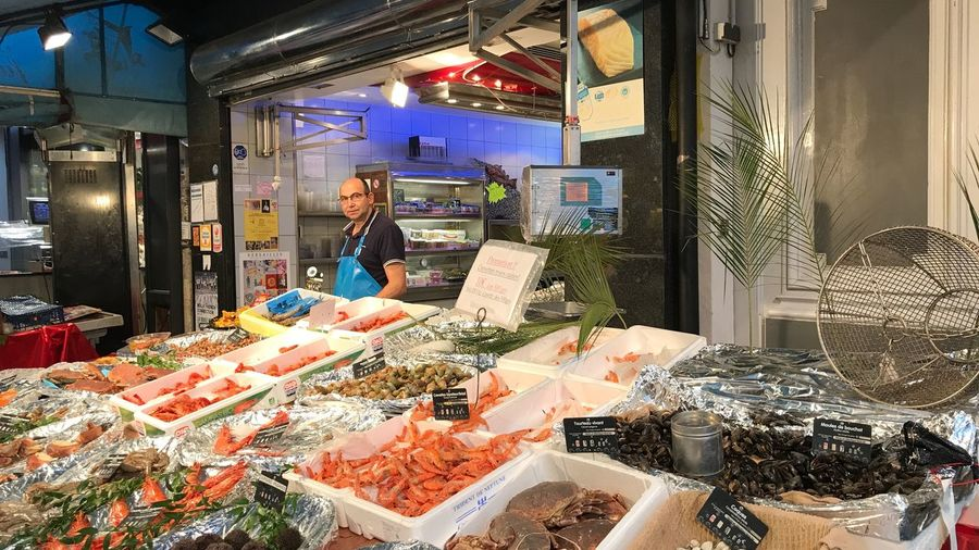 Fish seller Food Market Market Streetphotography Paris Selling Fish Fisherman One Person Retail  Real People Store Indoors  Lifestyles Choice For Sale Men Illuminated Business Shopping Variation Standing Retail Display Consumerism