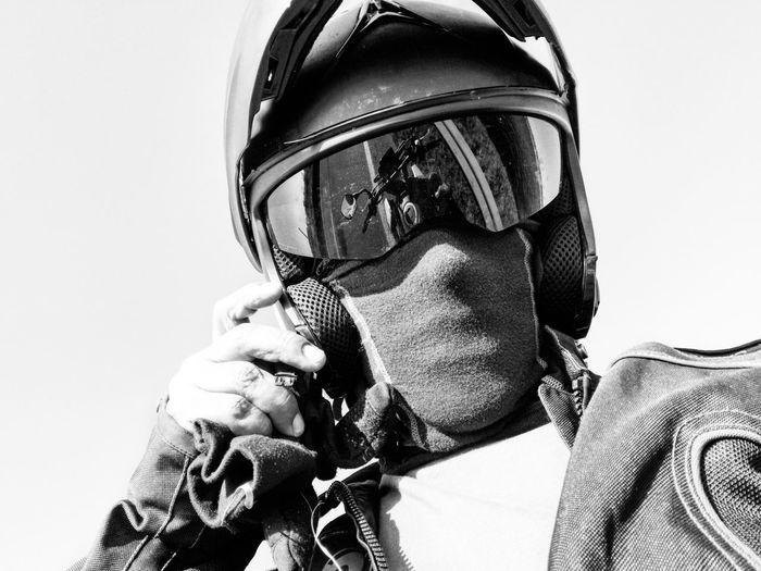 Low Angle Portrait Of Biker Wearing Helmet Standing Against Clear Sky
