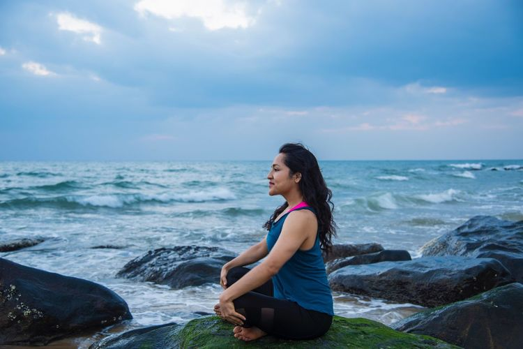 Woman Meditating On Shore Against Sky