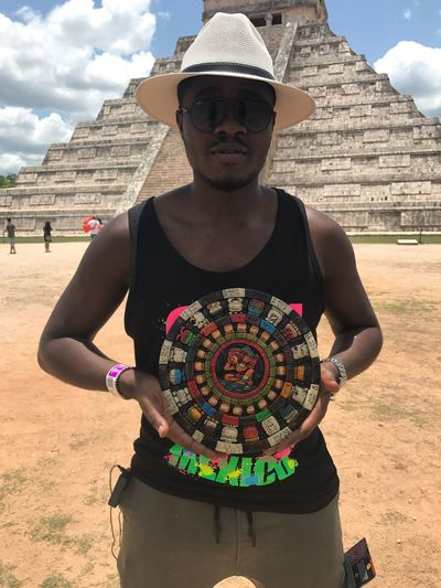 Young man holding mayan artifact against el castillon pyramid