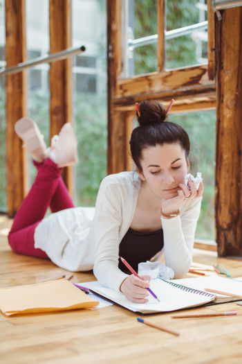 Woman drawing in book while lying on hardwood floor