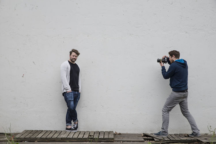 Full length of photographer photographing man leaning on wall