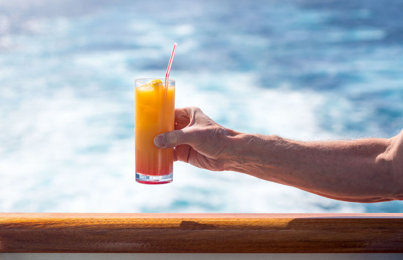 Cropped hand of man having drink on boat in sea
