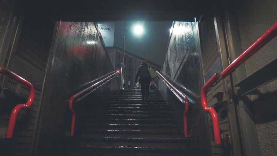 Low Angle View Of Woman Walking On Steps At Night