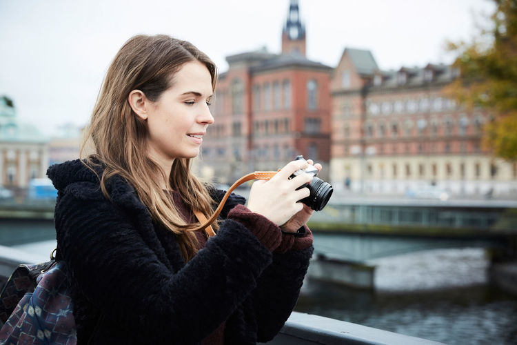 Young woman using smart phone in city during winter