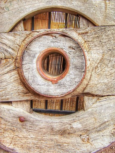 Old wooden wheel with insert against vertical lines. No People Architecture Built Structure Close-up Day Outdoors Nature Old Wood Wheel Wood - Material Aged Beauty Metal EyeEmNewHere Wood Grain Editorial  Worn Out & Wonderful  Backgrounds Antique Close Up Wagon Wheel Covered Wagon Wheel