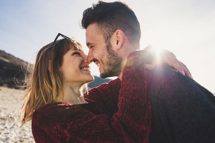 Close-up of happy couple standing against sky