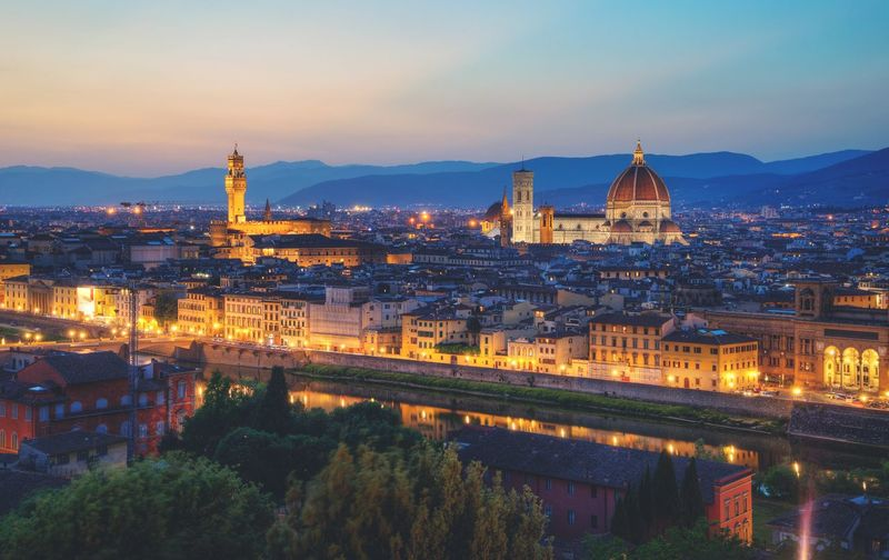High angle view of duomo santa maria del fiore amidst buildings in illuminated town at night