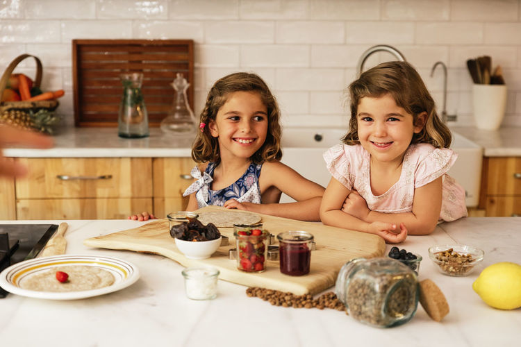 Childhood Child Togetherness Indoors  Women Girls Cooking Kitchen Chocolate Daughter Sisters Happy Family Home Copy Space People Blonde Caucasian Fun Love Food Healthy Recipe Lifestyle Looking At Camera