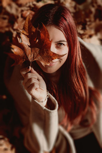 Portrait of woman with red leaves during autumn
