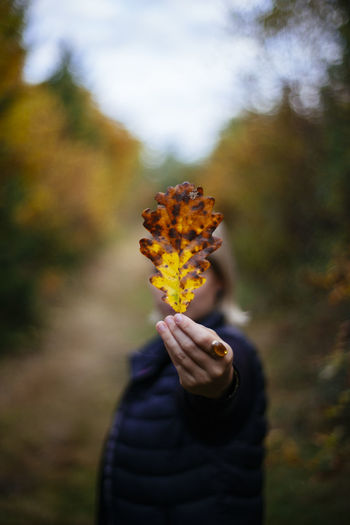 Woman showing autumn leaf in park