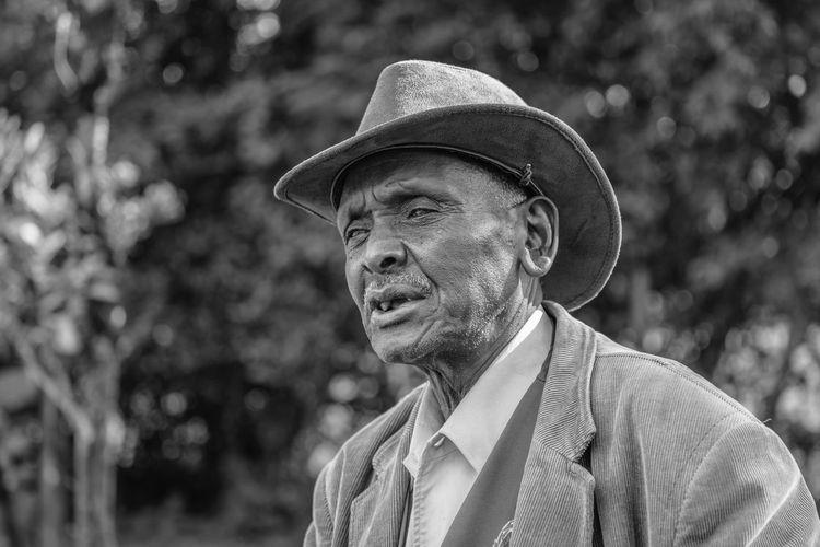 Portrait of man wearing hat looking away outdoors