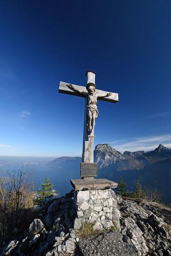 Cross on rock against blue sky