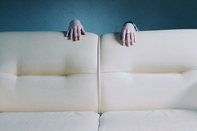 Cropped Image Of Woman Hand On Sofa