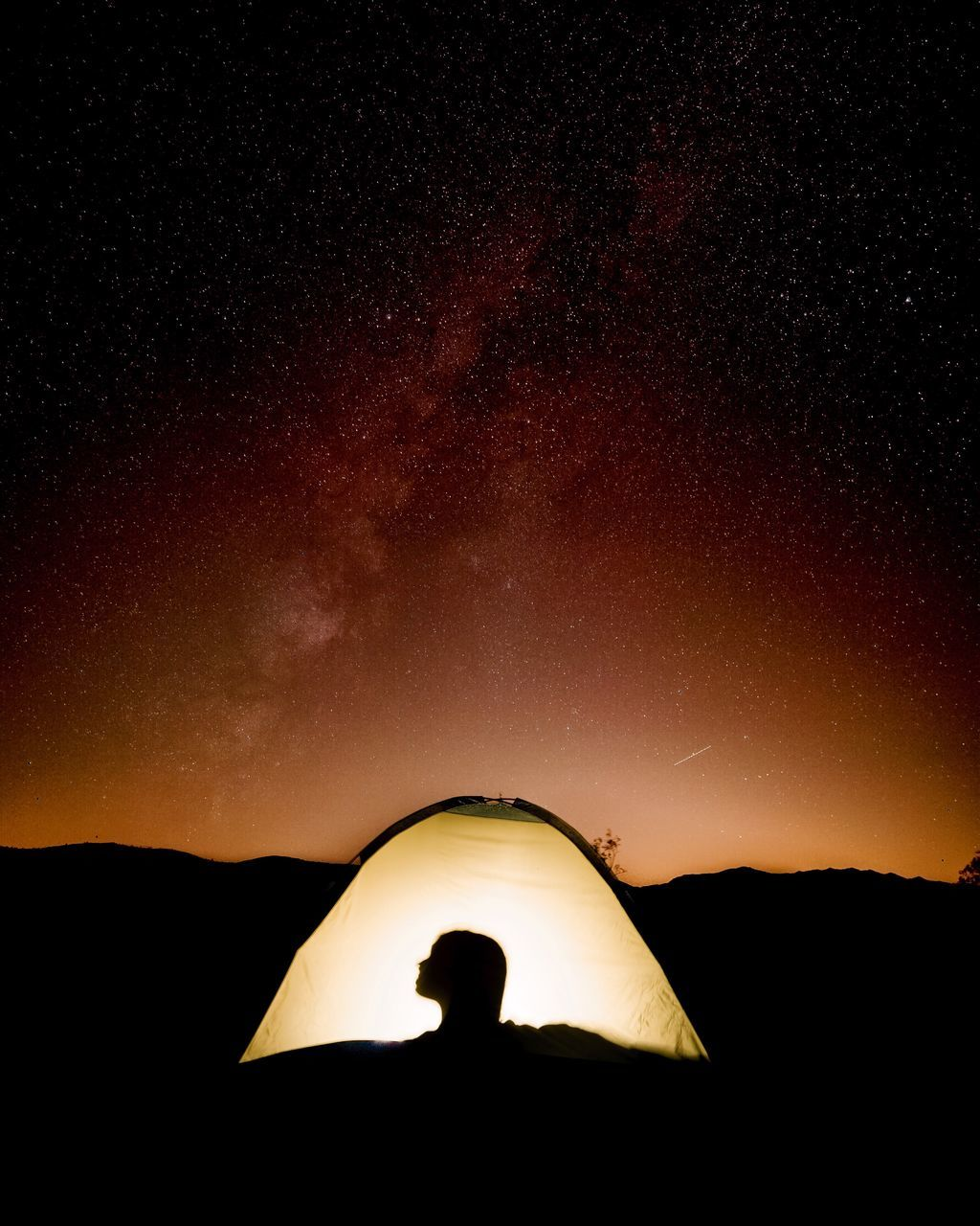 Shadow Of Person In Illuminated Tent Against Star Field At Night
