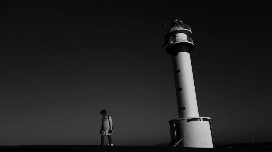 Man Standing By Lighthouse Against Clear Sky
