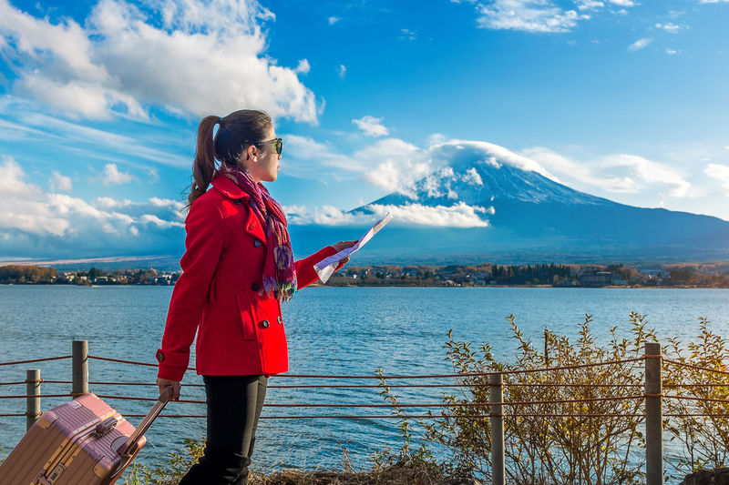 Young Woman With Luggage Standing By Lake Kawaguchi Holding Map