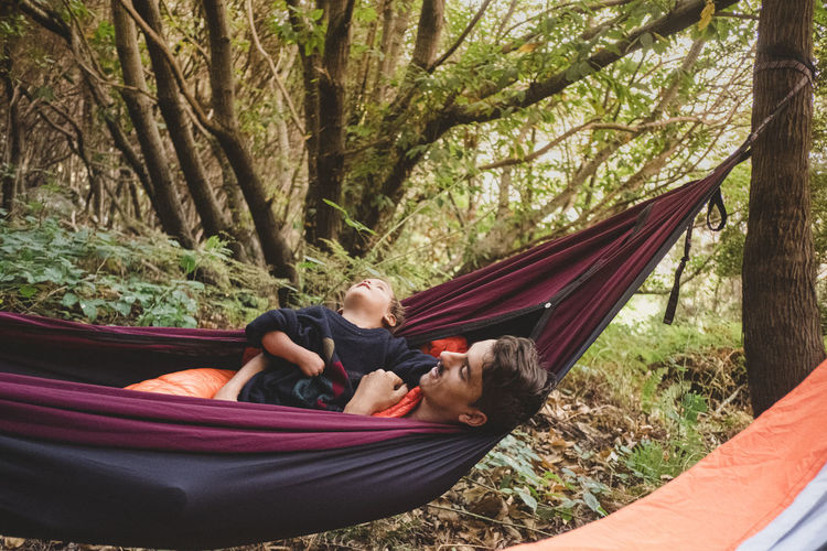 People relaxing on hammock in forest