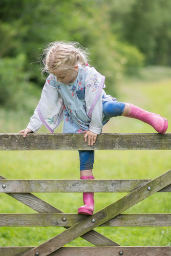 Cute girl climbing on wooden fence