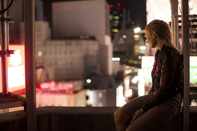 Side view of woman sitting in city at night