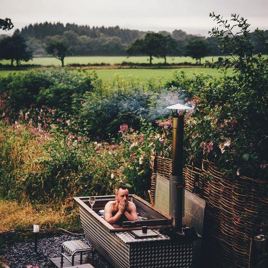 Man bathing in bathtub at front or back yard