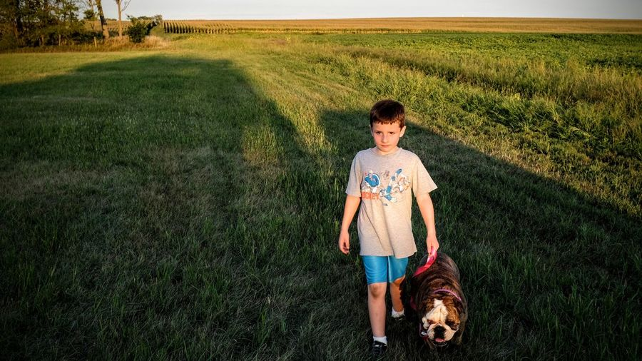 Full Length Of Boy Standing With Dog On Field