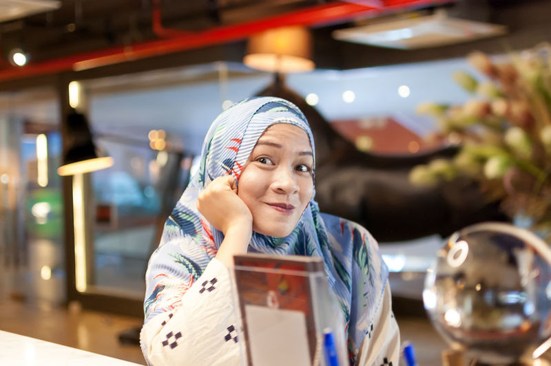 Portrait of smiling mid adult woman wearing hijab in store