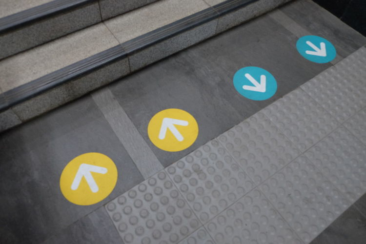 Sign at station MRT Jakarta Communication Sign High Angle View Symbol Guidance No People Directional Sign Yellow Arrow Symbol Information Sign Information Architecture Road Sign Direction Road Shape Pattern