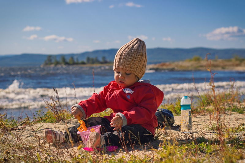 Moments of outgoing autumn. Child playing with sand on a lake beach on a sunny day. EyeEm Best Shots - Nature Portrait Photography Blue Sky Mountain Range Waves Sitting Childhood Child Water Beach Leisure Activity Lifestyles Outdoors Clothing Hat Nature Babygirl Babyhood Sandy Beach Sand Lake Autumn Autumn Collection September Sand Games Sand Play Game Playing Sunday PeopleZiesel777
