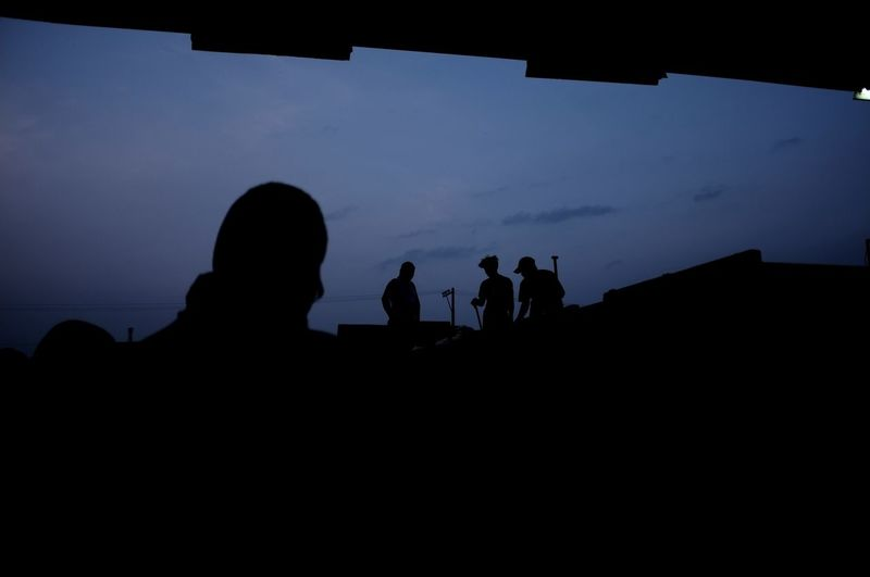 Silhouette Men On Field At Dusk